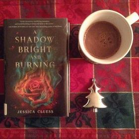 Day 2 of #decbookstagram Warm drink with a book! I'm still feeling under the weather today so I'm going to curl up with this hot chocolate and fantastical read by #jessicacluess How are you all doing?  #decbookstagram #bookstagram #readingwithrendz #pagewithaview #readwithmikee #reading #ashadowbrightandburning